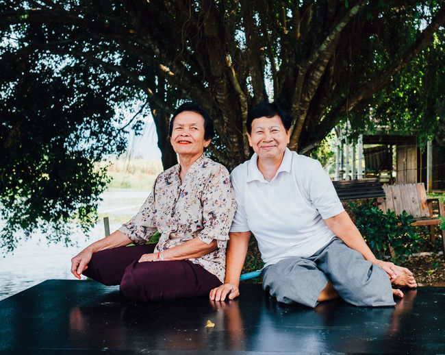Portrait of smiling couple sitting on tree