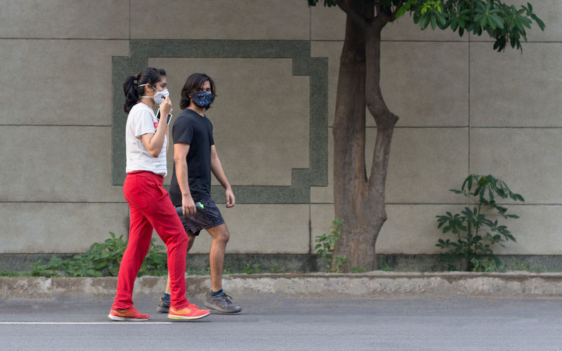 Side view of couple wearing mask walking on road
