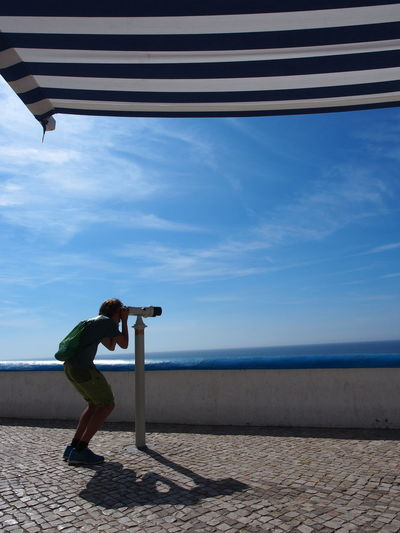 Man looking through coin-operated binoculars by sea against sky