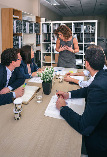 Businesswoman talking in a business meeting to teamwork sitting at table in company headquarters Business Company Innovation Man Meeting Office Teamwork Woman Working Workplace Business Finance And Industry Businessman Businesspeople Businesswoman Colleague Connection Group Headquarters Leadership Networking People Sharing  Success Team Vertical