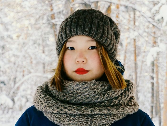 Portrait of woman wearing knit hat and woolen scarf during winter