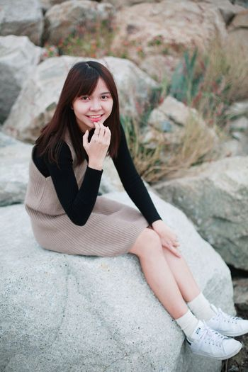 Portrait Of Smiling Young Woman Sitting On Rock At Beach