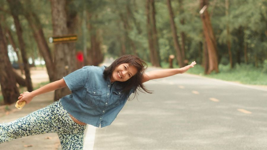 Young woman with arms raised on road against trees