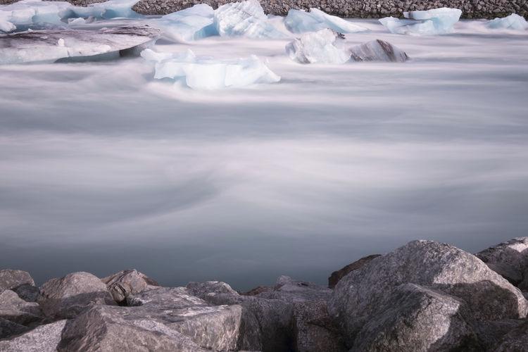 Scenic view of iceberg in lake against sky