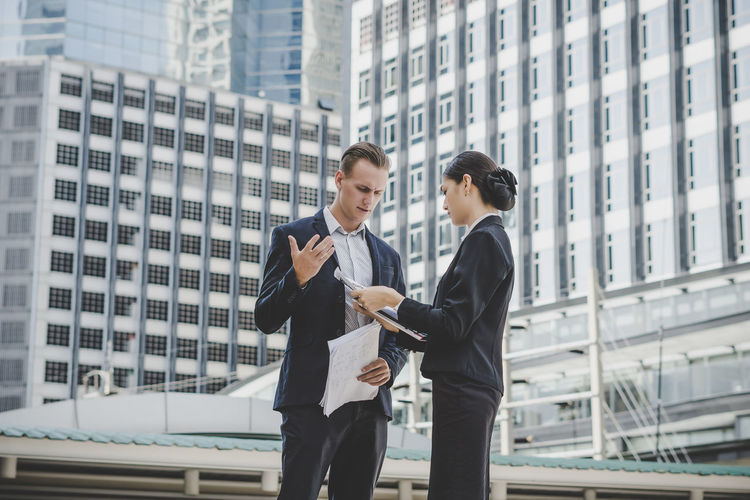 Business People Discussing While Standing Against Building