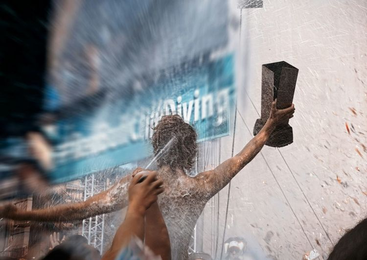 Cropped image of man spraying water on sport player holding trophy in city
