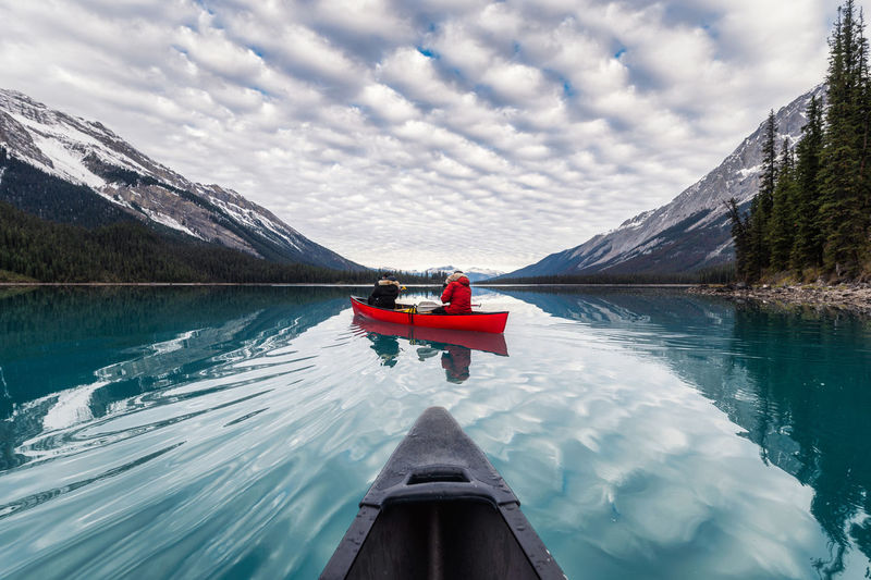 People in canoe on lake by mountains against sky