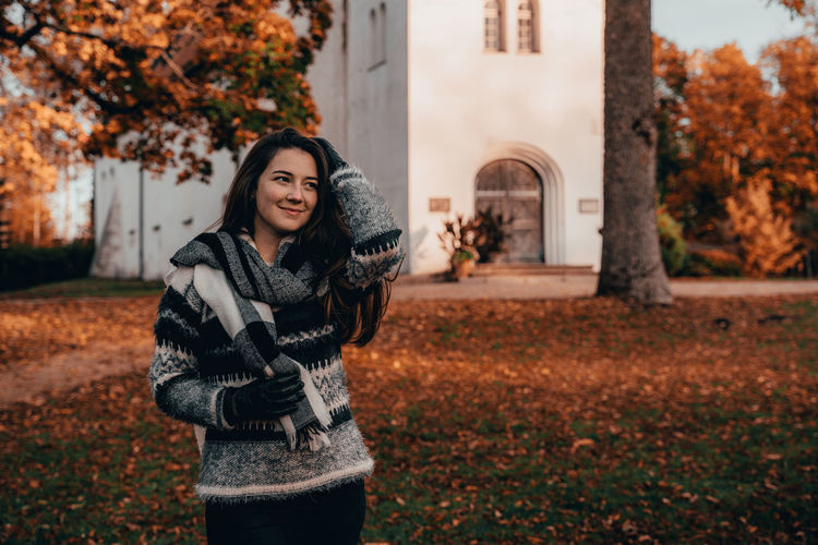 Smiling woman standing in park during autumn