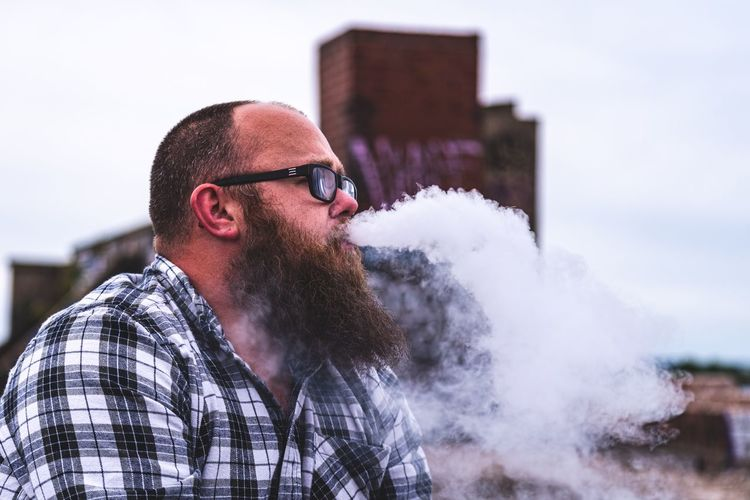 Man exhaling smoke while sitting against sky