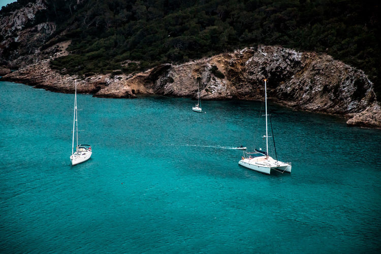 Ibiza, Spain Anchored Beauty In Nature Day Land Luxury Mode Of Transportation Nature Nautical Vessel No People Outdoors Rock Rock - Object Rock Formation Sailboat Sailing Scenics - Nature Sea Solid Transportation Travel Turquoise Colored Water Yacht Yachting Mast