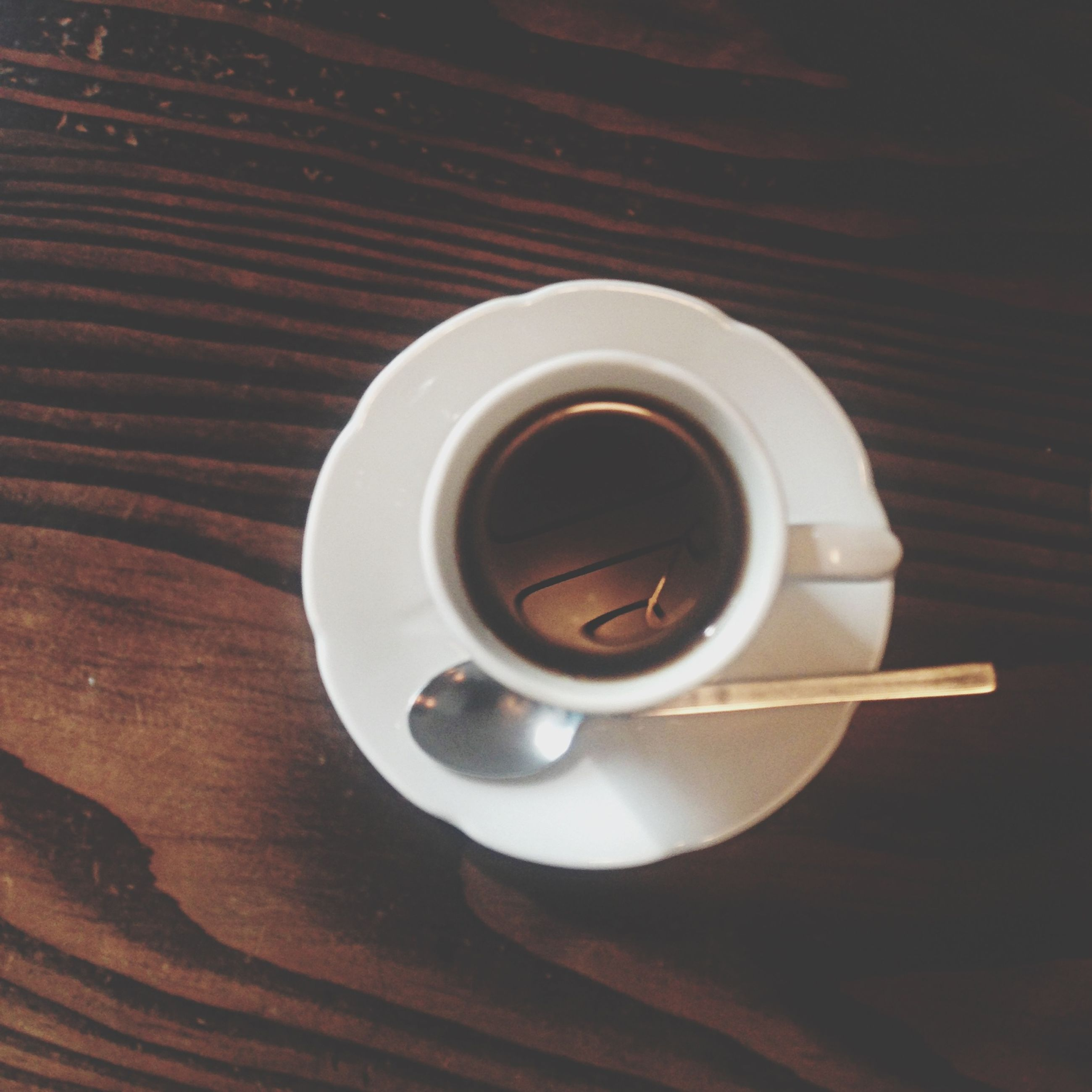 coffee cup, indoors, drink, coffee - drink, table, refreshment, saucer, still life, directly above, food and drink, coffee, high angle view, cup, close-up, wood - material, freshness, no people, spoon, overhead view, black coffee