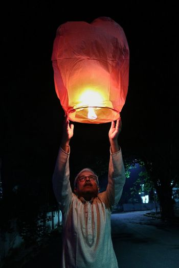 Midsection of man with illuminated lantern at night