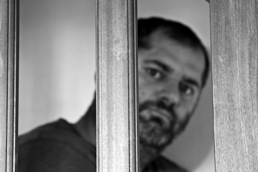 Portrait One Person Headshot Focus On Foreground Looking At Camera Window Close-up Emotion Adult Peeking Indoors  Men Metal Entrance Door