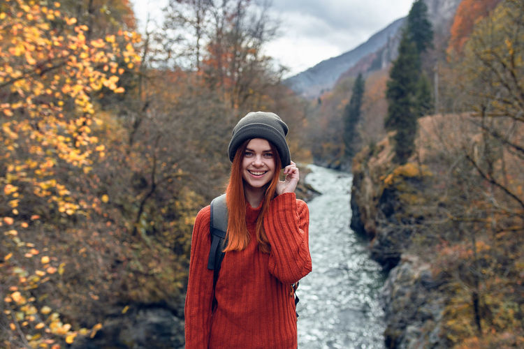 Portrait of smiling young woman standing during autumn