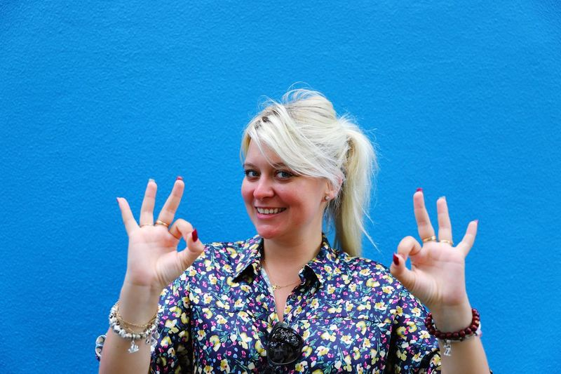 Portrait of smiling young woman gesturing ok sign against blue wall