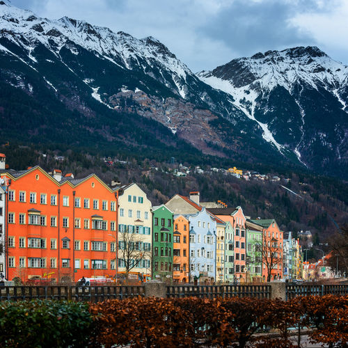 Houses by mountain against sky during winter