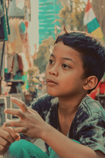 Portrait of boy holding mobile phone outdoors