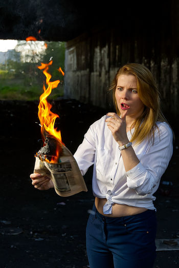 Young woman holding burning paper outdoors