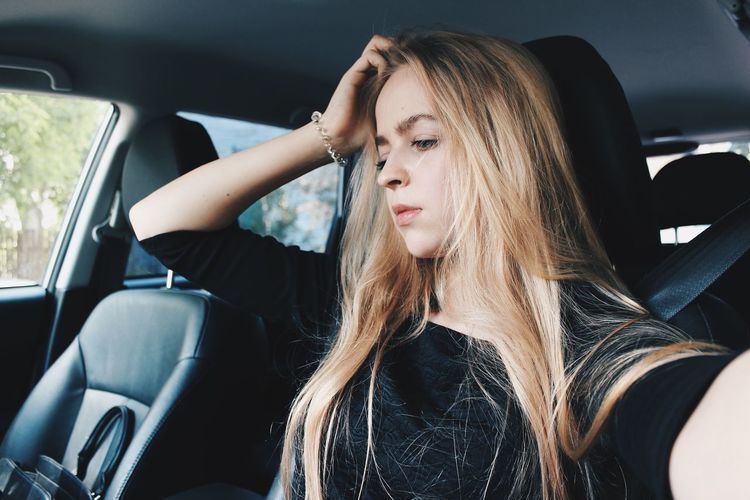 Thoughtful young woman sitting in car