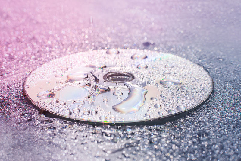 Close-Up Of Raindrops Compact Disc On Surface