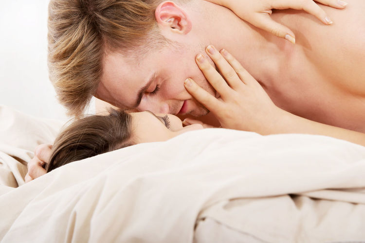 Affectionate shirtless couple kissing while lying on bed at home