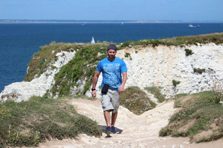 Portrait of man on rock by sea
