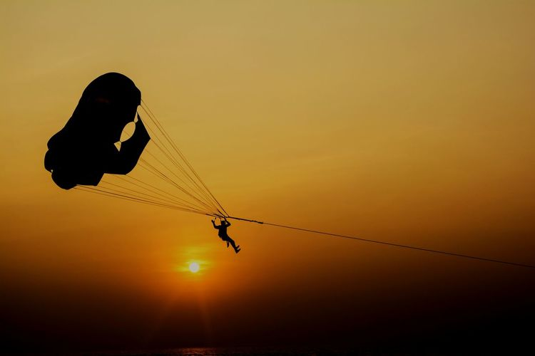 Silhouette person paragliding against clear sky during sunset