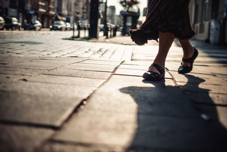 Low section view of woman walking on sidewalk