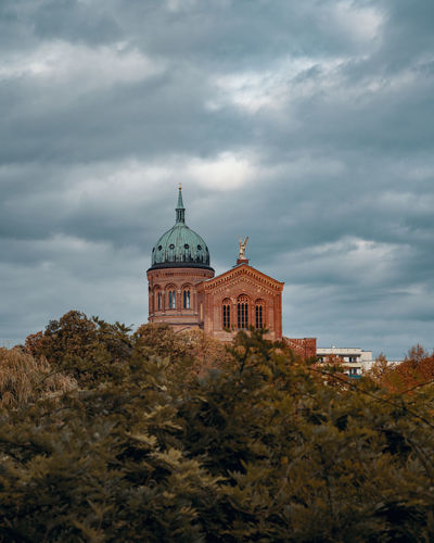 Low angle view of trees and church against cloudy sky