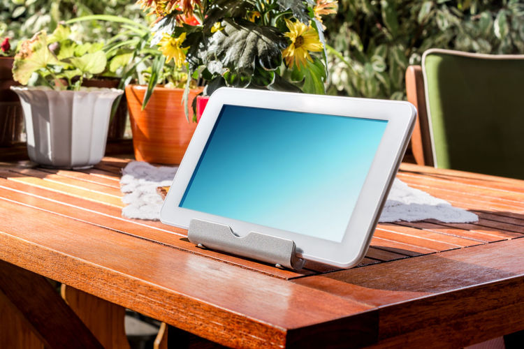 White Business Tablet Standing On A Wooden Table On A Sunny Summer Day Autumn Bright Business Patio Reflection Standing Sunlight Sunny Tablet Wood Work Blank Close-up Colorful Computer Flowerpots Garden Homework Metal Outdoors Portable Sky Spring Table Wireless