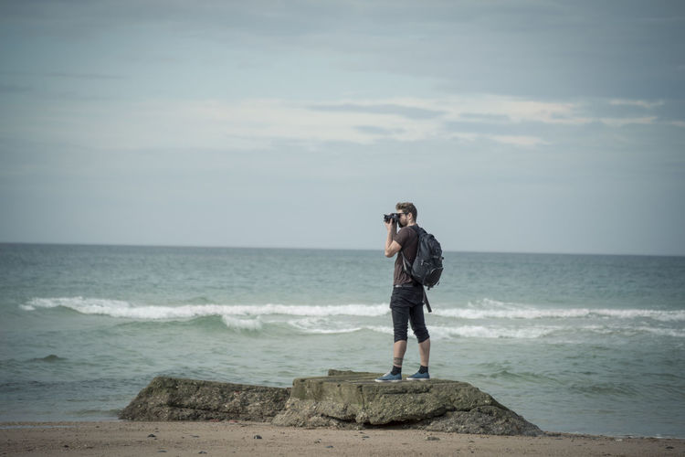 Full Length Of Photographer Photographing At Beach Against Sky