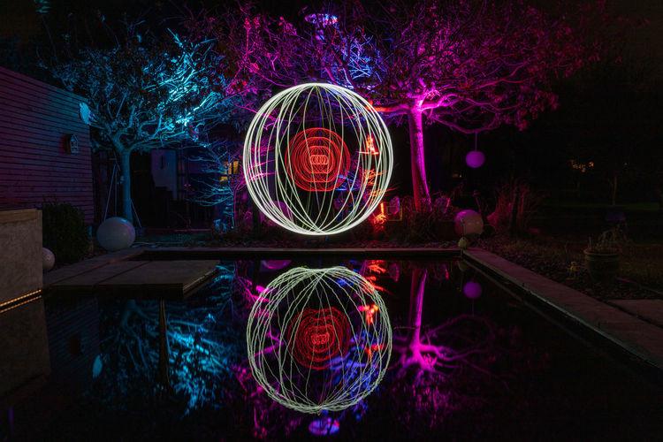 Illuminated light painting on tree at night