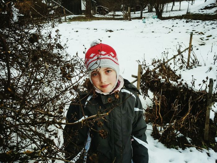 Portrait of girl standing by tree on snowfield