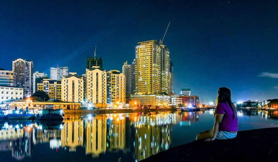 Woman sitting at riverbank against illuminated buildings in city