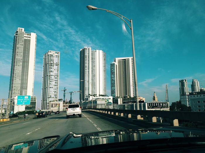 Road By Buildings Against Sky Seen Through Windshield
