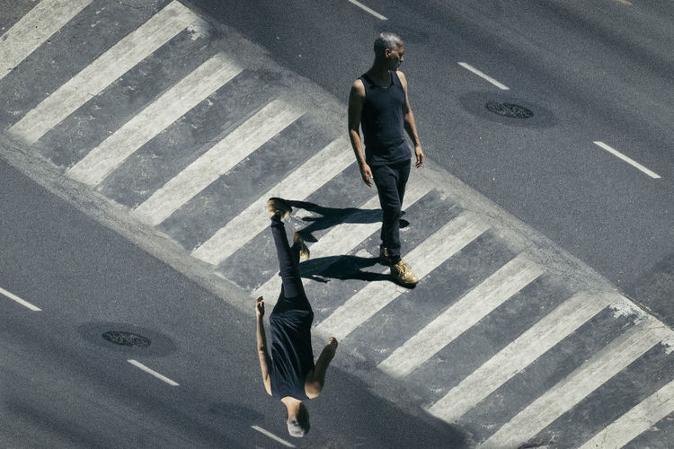 Optical illusion of man walking across street, crossing at a crosswalk Indecision City Crossing Crosswalk Day Full Length High Angle View One Man Only One Person Optical Illusion Outdoors Road Road Marking Street Walking