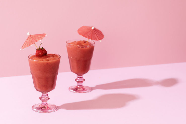 Close-up of drink served on table against pink background