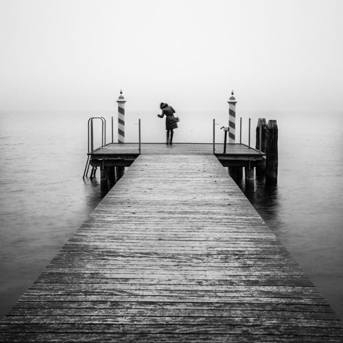 B&W jetty on a lake Beauty In Nature Blackandwhite Clear Sky Horizon Over Water Italia Italy Jetty Jetty Area Jetty View Lake Lake View Lakescape Lakeside Landscape Longexposure One Person Pier Silence The Way Forward Tranquil Scene Tranquility Water