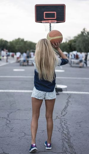 Rear view of young woman playing basketball