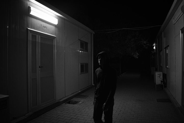 Man standing in illuminated building at night