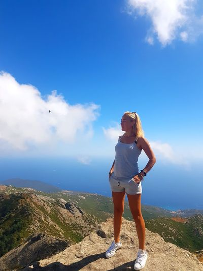 Full length of woman standing by cliff against sky