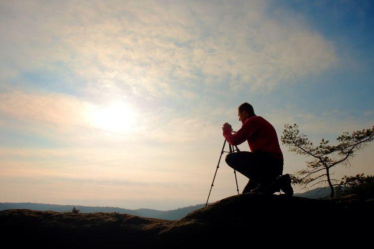 Nature photographer with tripod on cliff and thinking. dreamy fogy landscape, orange misty sunrise