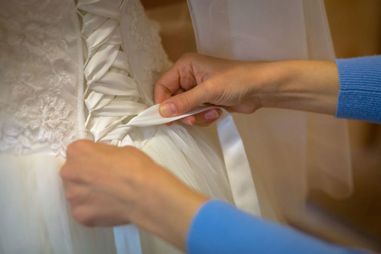 Cropped Hands Of Woman Tying Ribbon To Dress