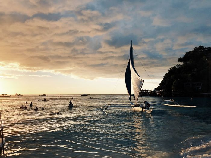 People In Sailboats On Sea Against Sky