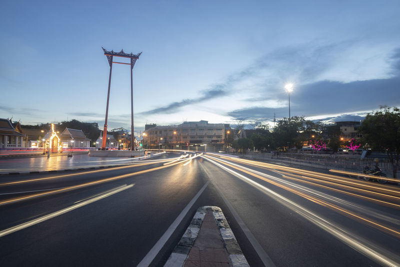 Light trails on highway in city against sky