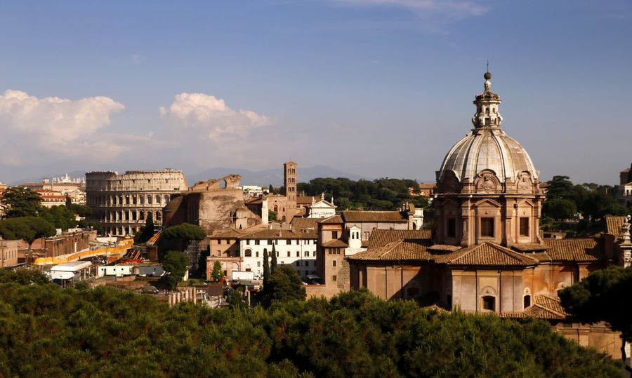An aerial view of Rome with the church of Santi Luca e Martina in the foreground with the imposing Coliseum in the background. Church Cityscape Coliseum Travel Travel Photography Aerial View Of City Ancient Architecture Belief Building Building Exterior Built Structure City Dome History Nature No People Outdoors Place Of Worship Religion Spirituality The Past TOWNSCAPE Travel Travel Destinations