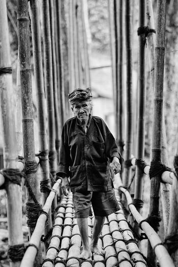 Full length of senior man walking on bamboo footbridge
