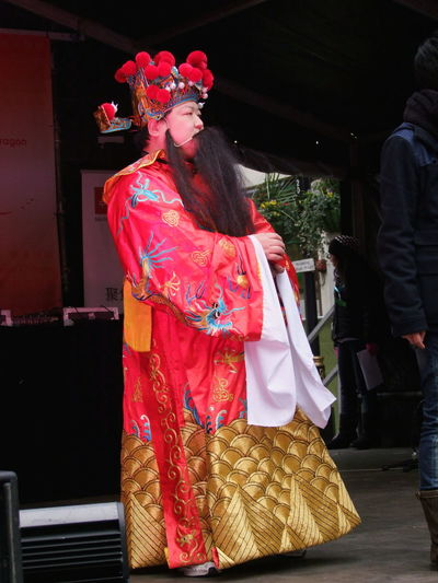 Chinese Money Man Business Chinese New Year 2012 Composition Cultures Full Length GB Gold Colour Lifestyles London Money Man Occupation Portrait Real People Red Colour Side View Smiling Standing Tradition Traditional Clothing Urban Young Adult