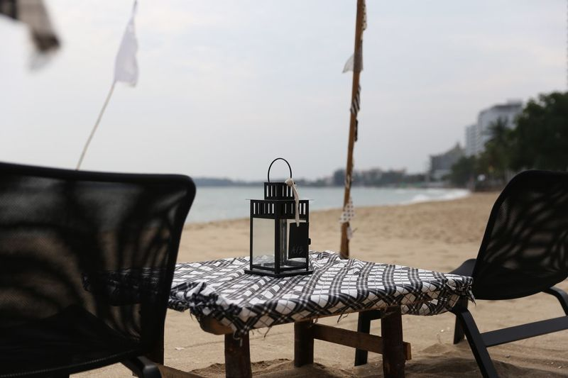 Chairs and table at beach against sky