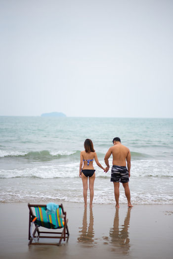 Sea Beach Water Land Two People Rear View Swimwear Holiday Copy Space Horizon Horizon Over Water Standing Trip Vacations Bikini Sky Clothing Adult Women Full Length Couple - Relationship